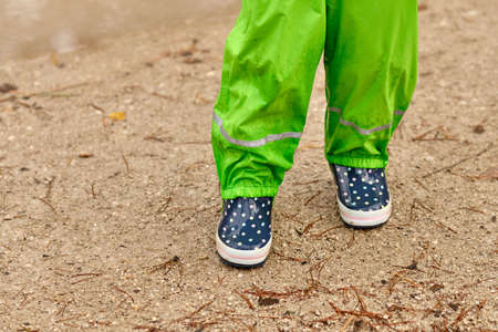 A child in green waterproof pants and spotted blue rubber boots standing on a wet gravel road in the forest on a rainy day in October in Germany Banque d'images