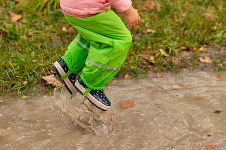 Low section of a child girl in green waterproof pants and rubber boots jumping into a massive rain puddle on a rainy autumn day in October in Germany Banque d'images