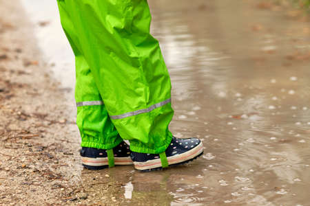 Low section of a child girl in green waterproof pants and rubber boots standing at a huge rain puddle in the forest on a rainy autumn day in October in Germany