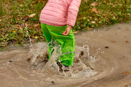 Low section of a child girl in green waterproof pants and rubber boots jumping into a massive rain puddle with the water splashing high up in the air on a rainy autumn day in October in Germany