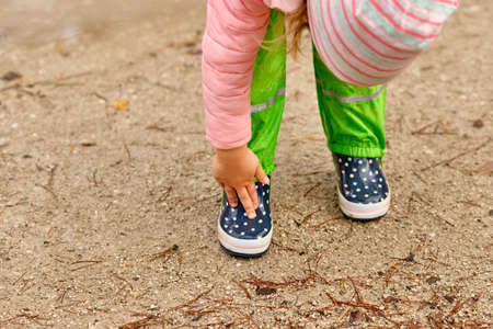 A child in green waterproof pants and spotted rubber boots standing on a wet gravel road in the forest and touching her boots with her fingers on a rainy day in October in Germany