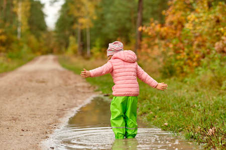 Rear view of a caucasian child girl with the arms strechted out in green waterproof pants and rubber boots standing in a huge rain puddle alongside a gravel road in the forest on a rainy autumn day in October in Germany