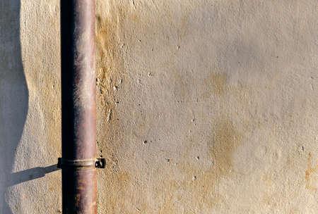 Rain gutter on a sunany wall of a house.