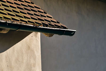 A roof of an old house and a rain gutter on a sunny day in March in Germany