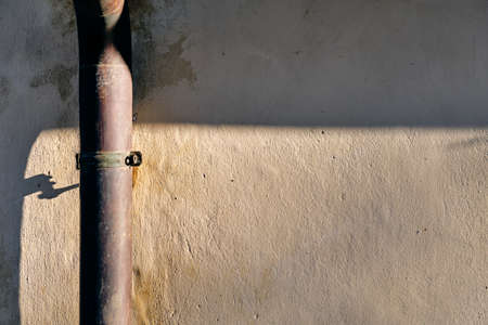 Rain gutter on a sunny wall of a house.