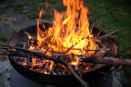 A natural bonfire with wooden sticks and branches is burning in a fire bowl at night. Seen in Germany in July. Banque d'images