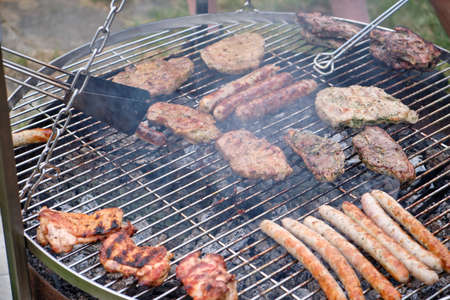 Red meat, white meat and bratwurst being grilled on a cooking grate of a big grill. Seen in Germany in July.