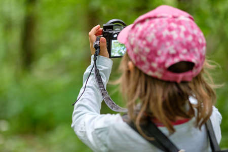 Nuremberg, Germany - June 22, 2020: Rear view of a 4 year old European child girl with cap taking photos with her digital camera in the green forest Éditoriale