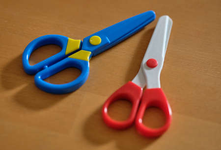 Two colorful blue, red and white colored chidrens scissors are lying on a wooden table