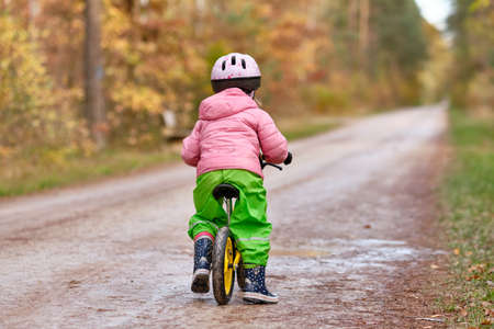 Rear view of a child girl riding on her balance bicycle in warm and waterproof clothing on a wet and dirty gravel road in the autumn forest. Lakes in Franconia / Bavaria in Germany in November. Banque d'images