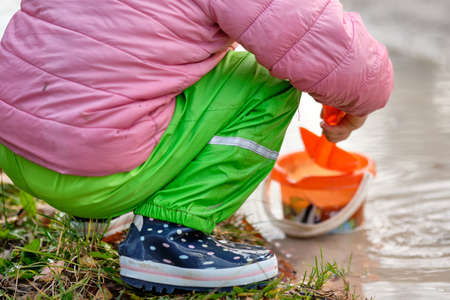 Low section of a child with rubber boots and waterproof pants playing in a deep muddy rain puddle with a shovel and a bucket. Lakes in Bavaria in Germany in November