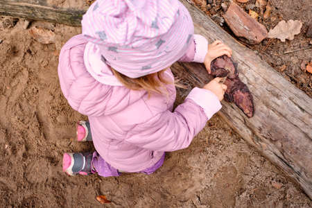 Cute child girl playing with wood and a piece of bark on a playground in the forest wearing warm clothes in autumn. Seen in Germany, Bavaria in October.
