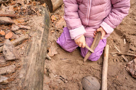 Low section of a child girl playing with wood on a playground in the forest wearing warm clothes in autumn. Seen in Germany, Bavaria in October.