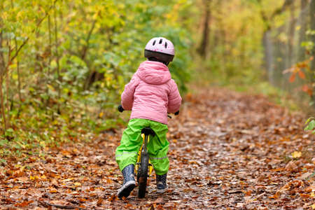 Rear view of a 4 year old child girl riding on a footpath through an autumnal forest in Franconia / Bavaria in Germany in October