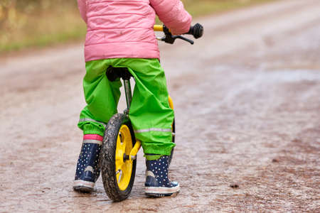 Rear view of low section of a child girl sitting on her balance bicycle in warm and waterproof clothing on a wet and dirty gravel road in autumn. Lakes in Franconia / Bavaria in Germany in November. Banque d'images