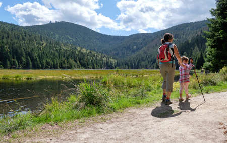 Lohberg, Germany - August 26, 2020: A woman is hiking with her young daughter around the beautiful Kleiner Arbersee with a view on the mountain Großer Arber in the background in summer Éditoriale