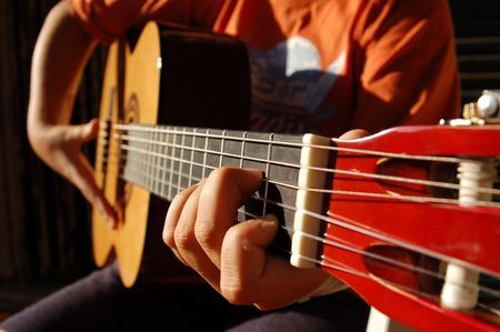 A boy performs a song with the guitar Stock Photo
