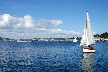 A sailboat enters the harbor Camaret - Brittany - France Stock Photo