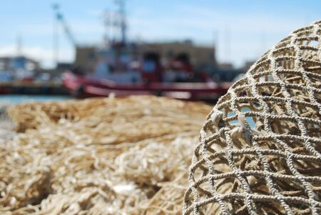 A fishing net with Large mesh vessels moored in the backgroundi Stockfoto
