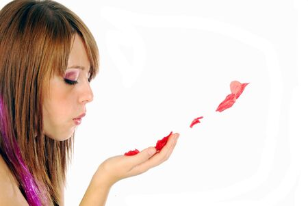 A young girl blowing on rose petals Stock Photo - 9645890