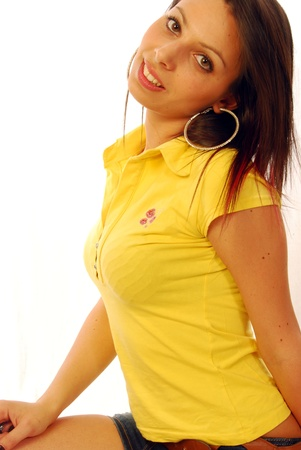 shorts t shirt sexy: A beautiful and sexy brunette in a yellow T-shirt Stock Photo