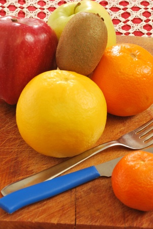 A group of oranges, grapefruits, tangerines, apples and kiwi fruit for a healthy and nutritious breakfast photo