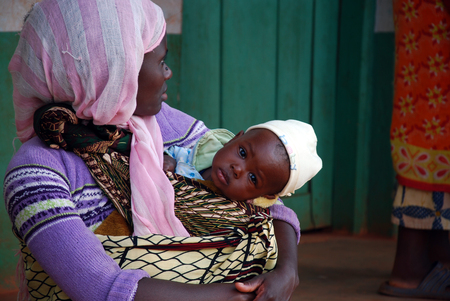 August 2014 - Village of Pomerini - Tanzania - Africa - An African woman with her child. received into the Franciscan Mission for Humanitarian Aid for Aids Editorial