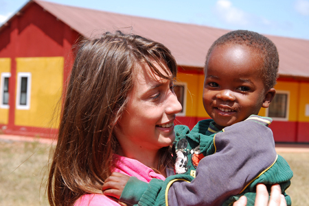 August 2014-Village of Pomerini-Tanzania-Africa-A voluntary non-profit organization Smile to Africa plays with a small African child of the Village of Pomerini in Tanzania.