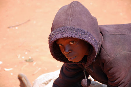 August 2014-Pomerini-Tanzania-Africa-An African child at home while transporting towards a bag of merchandise with a rudimentary wheelbarrow, Often are only children to carry on the hard work Redactioneel