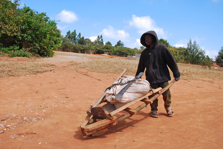 humanitarian aid: August 2014-Pomerini-Tanzania-Africa-An African child at home while transporting towards a bag of merchandise with a rudimentary wheelbarrow, Often are only children to carry on the hard work Editorial