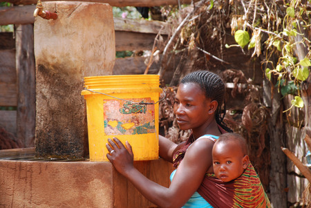 water's edge: August 2014-Franciscan Mission of Pomerini-Tanzania-Africa-A mother with her baby fill up a bucket of drinking water to the public fountain of the Franciscan Mission of Pomerini.