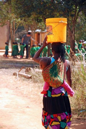August 2014-Franciscan Mission of Pomerini-Tanzania-Africa-A mother with her baby fill up a bucket of drinking water to the public fountain of the Franciscan Mission of Pomerini.