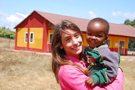 nonprofit: August 2014-Village of Pomerini-Tanzania-Africa-A voluntary non-profit organization Smile to Africa plays with a small African child of the Village of Pomerini in Tanzania. Editorial