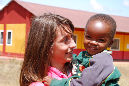 August 2014-Village of Pomerini-Tanzania-Africa-A voluntary non-profit organization Smile to Africa plays with a small African child of the Village of Pomerini in Tanzania. Editorial