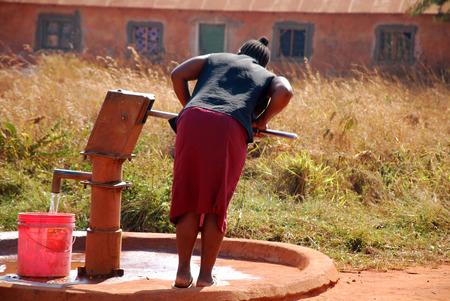 bomba de agua: Una mujer y bomba de agua de una fuente p�blica-Pomerini-Tanzania-�frica Foto de archivo