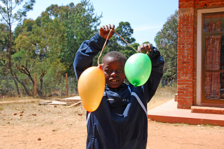 misery: 20-August-2014-Village of Pomerini-Tanzania-Africa-An African child plays with two colored balloons - between poverty and misery two balloons become a valuable and important game