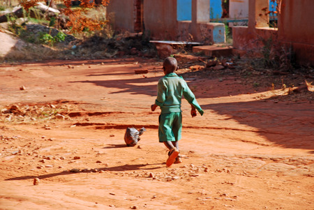 When there is a passion to play anywhere - An African child plays soccer with a ball of rags -Village of Pomerini - Tanzania - Africa photo