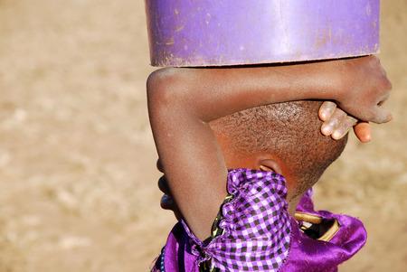 pobreza: Un niño africano con un cubo de agua - Pomerini - Tanzania - África - Una niña africana lleva en la cabeza un cubo de agua