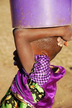 african solidarity: The bucket of water - Pomerini - Tanzania - Africa - A little African girl carries on his head a bucket of water