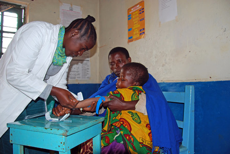 August 12, 2014-Pomerini-Tanzania-Africa-An unidentified child with his mother will submit to HIV tests in the dispensary of the village Pomerini in Tanzania, Africa, where more than a fifth of the population is sick