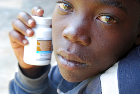 hiv virus: August 28, 2014 - Iringa-Tanzania-Africa-An unidentified child shows the antiretroviral drugs to fight the HIV virus; drugs just received from doctors at the hospital in Iringa; on her skin the signs of the disease Editorial