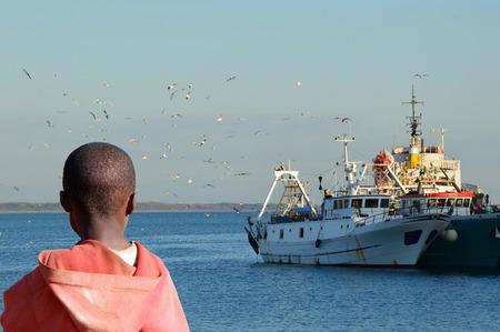 Un jour, je vais laisser trop - Un enfant africain regarde le navire qui, un jour, l'éloigner de l'Afrique Banque d'images - 44167228