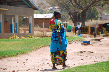clothes hanging: August 29, 2014, Ipamba Hospital of Iringa-Tanzania-Africa - An unidentified African pregnant woman walks in the courtyard of the Ipamba Hospital in the city of Iringa. The clothes hanging in the background that hospital patients wash and stretch yourself