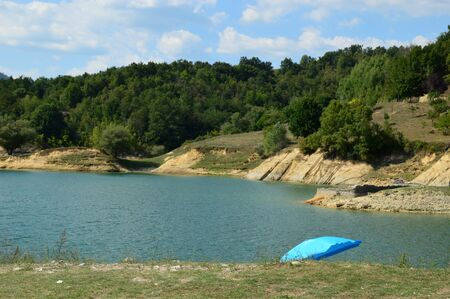 vacationers: Life of vacationers - A view of Lake Salto with an umbrella that sticking out from the coast