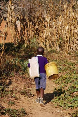 POBRES NI�OS: Un ni�o africano en su regreso a la escuela en los campos de la zona rural de la aldea de Pomerini Foto de archivo