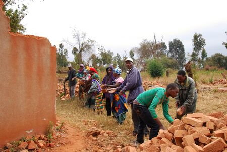 August 18, 2014, Village of Pomerini, Tanzania, Africa - An unidentified group family recovers red clay bricks still usable from a collapsed house in the village Pomerini, using the system of the human chain and pass from hand to hand Editorial