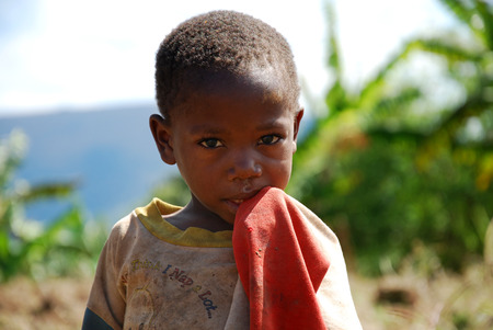 survives: August 8, 2014, Mountain Kilolo, Kilolo, Tanzania, Africa - The intense look of an unidentified African child of mountain Kilolo that survives thanks to the help of international NGOs and the Franciscan Friars who bring to their medicines, food and clothi Editorial