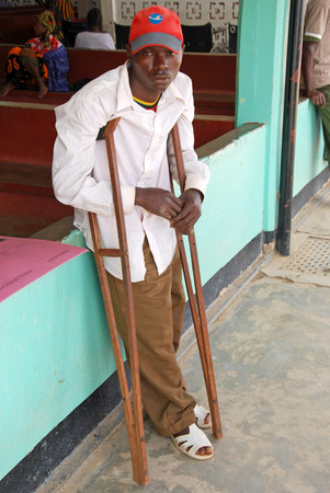 argued: August 8, 2014, Hospital of Iringa, Iringa, Tanzania, Africa - An unidentified African boy invalid to the leg is argued on crutches waiting to be visited by the orthopedic doctor for control of prostheses