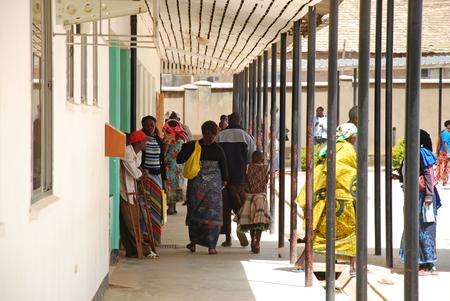 visitador medico: 8 de agosto de 2014, el Hospital de Iringa, Iringa, Tanzania, �frica - Un grupo no identificado de personas africanas cruzar la entrada del Hospital de Iringa, a la espera de ser llamado por los m�dicos para visitas y controles m�dicos