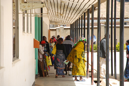 visitador medico: 8 de agosto de 2014, el Hospital de Iringa, Iringa, Tanzania, África - Un grupo no identificado de personas africanas cruzar la entrada del Hospital de Iringa, a la espera de ser llamado por los médicos para visitas y controles médicos